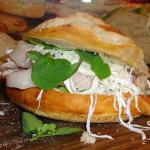 "A ""cemita"" sandwich being made at a restaurant in Puebla Mexico. The green leaves are pápalo."